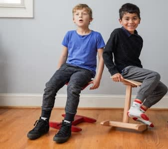 fully tic toc tyke red kids chair and natural Tic Toc chair in use by two kids