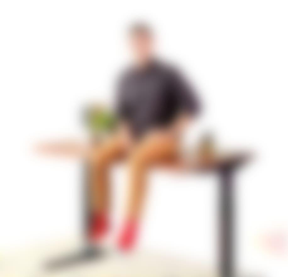 man sitting on jarvis adjustable standing desk smiling