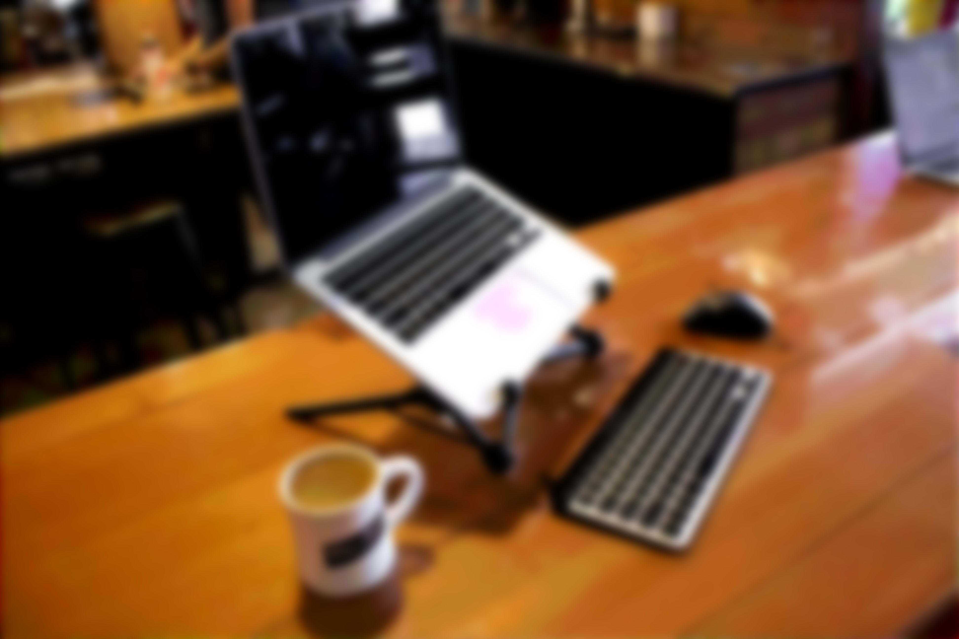 A roost with a computer on it being used at a coffee shop